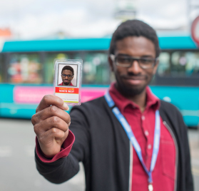 Picture of our student holding their bus pass.