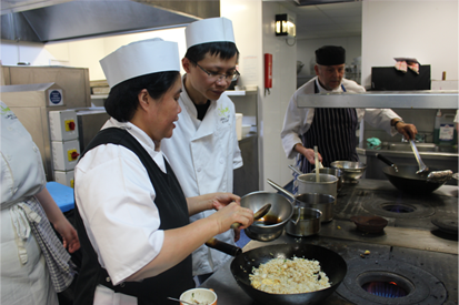 Picture of student learning with Charlie Chan in our kitchens