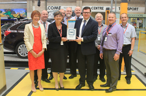 Conor McGinn MP (right) alongside IMI National Manager Michelle Barrett (left) presenting St Helens College Principal Jette Burford (middle) and staff with IMI award.